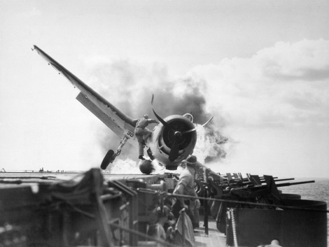 Lieutenant Walter L. Chewning, Jr. climbs aboard a crashed Hellcat to save pilot, Ensign Byron M. Johnson. USS Enterprise, November 10th, 1943.